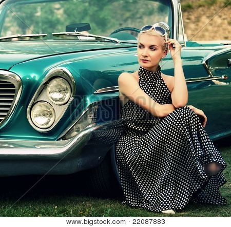 Beautiful lady sitting near retro convertible.
