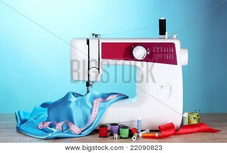 sewing machine and fabric on blue background