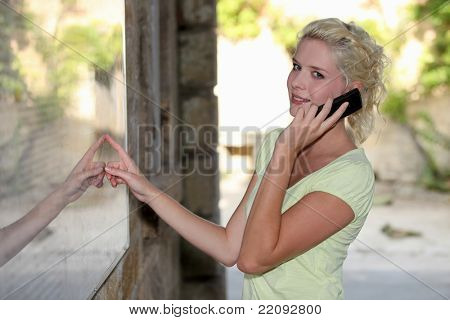 Blond woman outside restaurant using mobile telephone