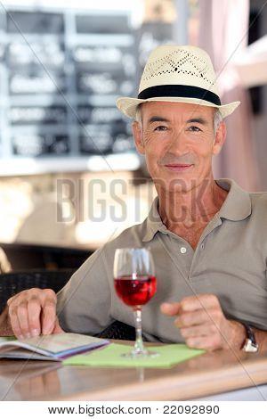 Older gentleman tourist drinking a glass of rose in a restaurant
