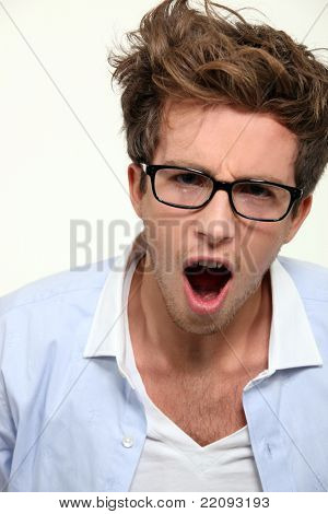Man in glasses yawning
