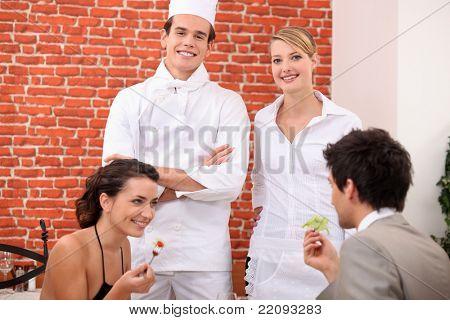 ein paar Speisen im Restaurant, ein Koch und eine Kellnerin hinter Ihnen