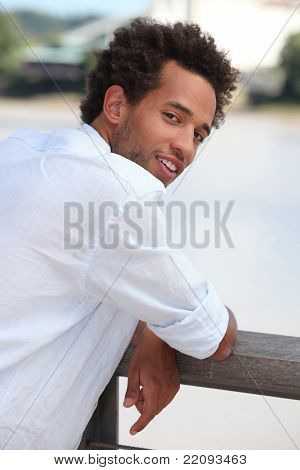 Young man leaning on a wooden fence