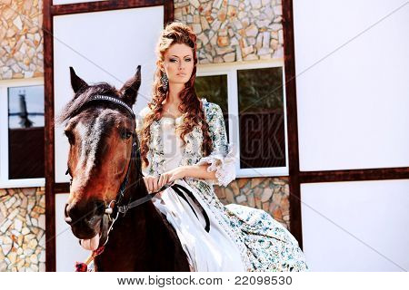 Beautiful young woman in medieval dress riding a horse outdoor.