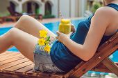 Young Woman Is Holding A Smoothie Of Mango On The Background Of The Pool. Fruit Smoothie - Healthy E poster