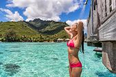 Luxury travel destination bikini woman taking an outdoor shower at luxury resort hotel overwater bun poster