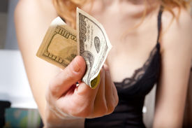 foto of streetwalkers  - Young woman holding a dollar banknote in her hand - JPG