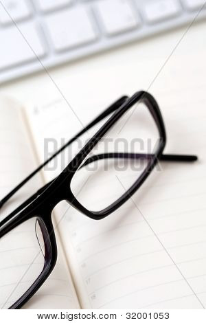 Gafas, el teclado y el papel de cuaderno