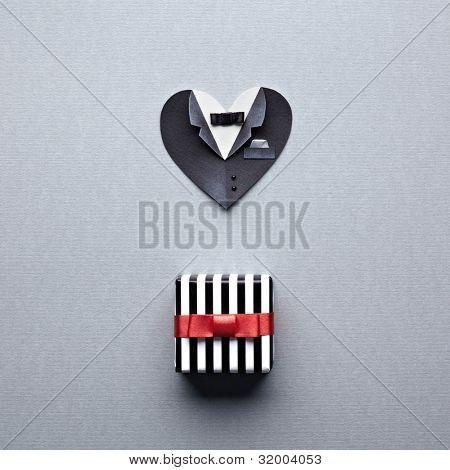 En forma de corazón hombre simbólico con caja de regalo había atado con lazo de seda rojo. Sobre papel gris. Boda o st.V