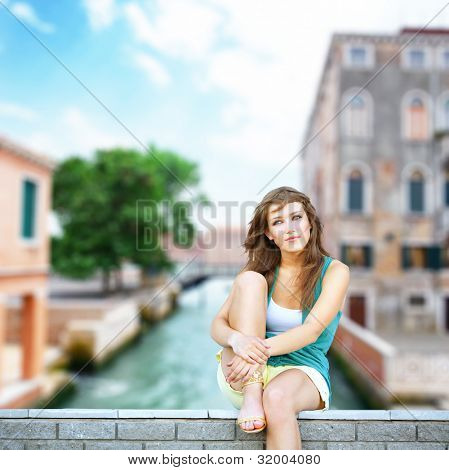 Cute student teenage girl sitting at urban scene in Venice. She is dreaming about something.