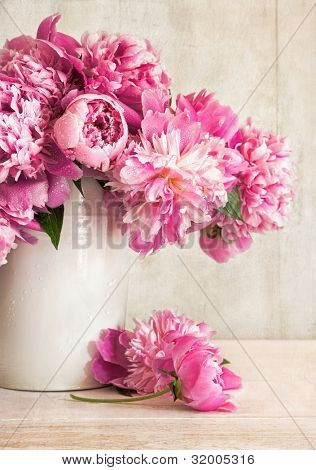 Peônias rosa em um vaso no fundo madeira