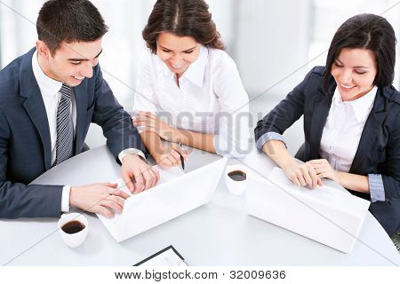 Young business people working on laptop in modern office