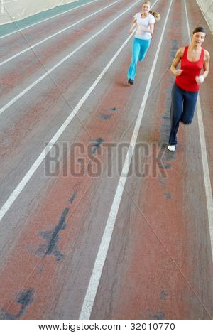 Blurred image of two girls running in gym