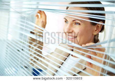 Smiling business woman looking out of the window with blinds