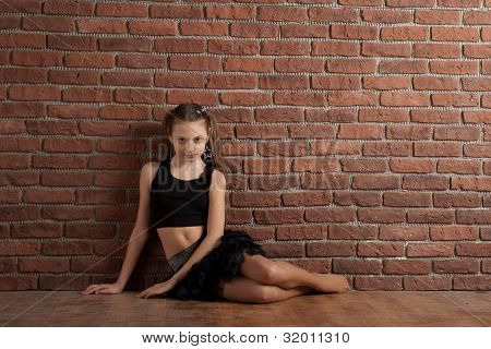 Girl Sitting Near Brick Wall