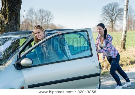 Vehicle breakdown two young women pushing car down the road