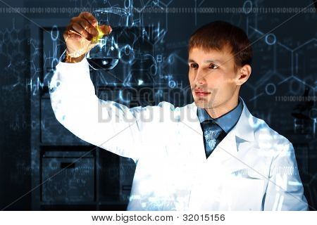 Young chemist in white uniform working in laboratory