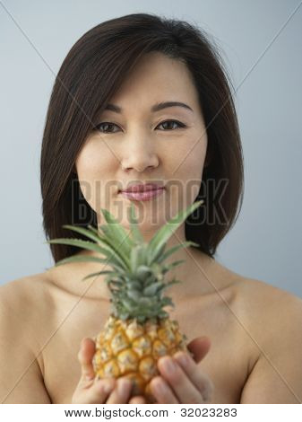 Asian woman holding pineapple