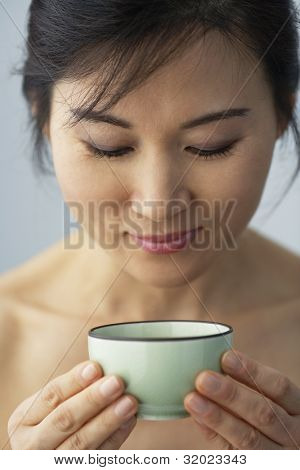 Asian woman holding tea cup