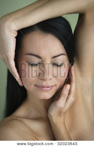 Asian woman with hands framing face