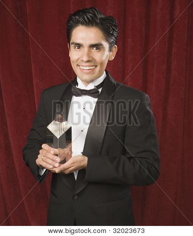 Portrait of Hispanic man holding award