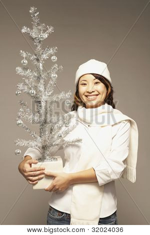 Portrait of Asian woman holding artificial Christmas tree
