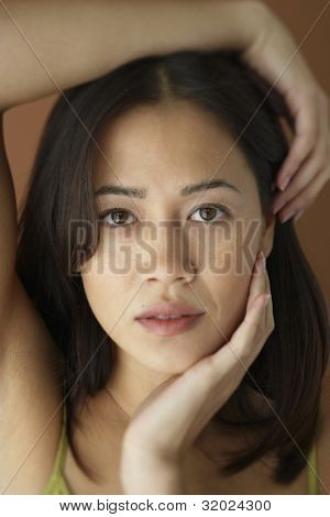 Asian woman with hand on face