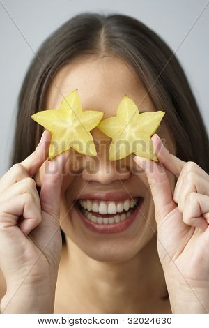 Asian woman holding star fruits over eyes