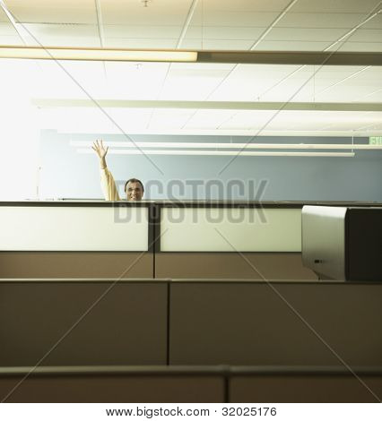 Businessman waving from behind partition