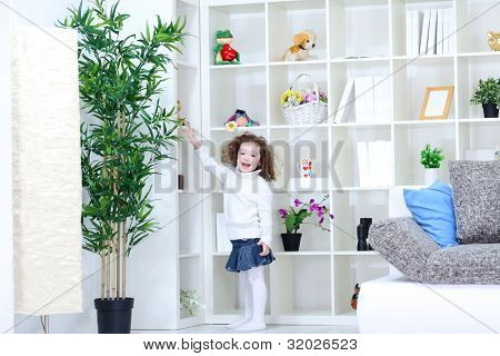 laughing little girl returns to the place of her toys after playing