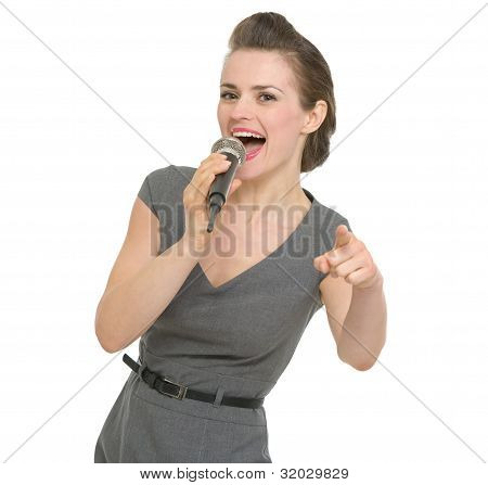 Happy Woman Singing In Microphone And Pointing On You Isolated