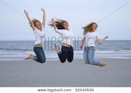 Girls Jumping For Joy On Beach