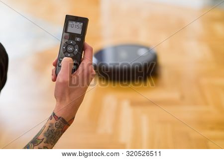 poster of Close up of man hands controling automatic vacuum cleaner using electronic control of the mopping ro