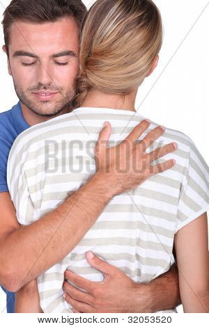 man with closed eyes embracing a blonde