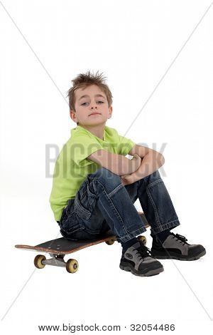 little boy sitting on his skateboard