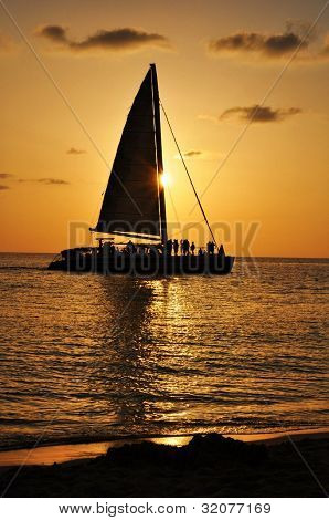 A boat in the sea passing the sunset in Jamaica