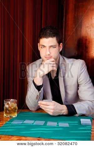 Latin handsome gambler man in table playing poker cards and drinking whisky