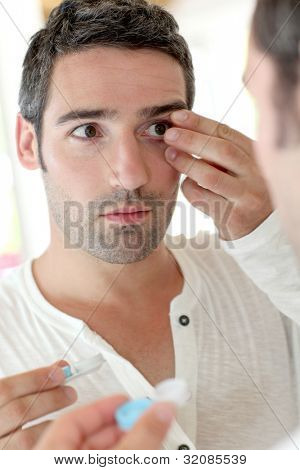 Man in front of mirrror putting ocular lens