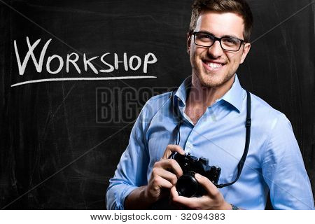 Smiling photographer in front of a blackboard