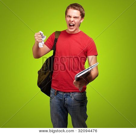 young angry student man roughing a sheet over a green background