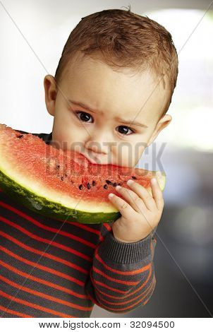 portrait of a handsome kid holding a watermelon piece and licking it, outdoor