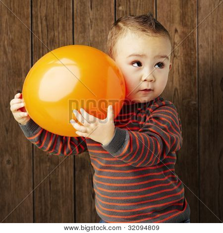 portrait of a funny kid holding a big orange balloon against a wooden background