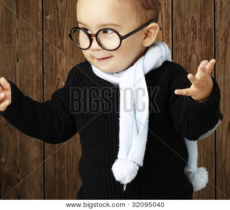portrait of an adorable kid wearing glasses gesturing doubt against a wooden background