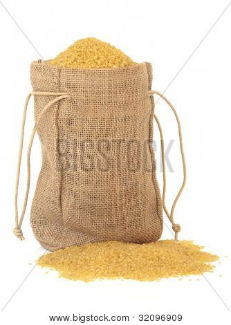 Bulghur wheat in a hessian sack over white background.