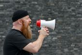 Angry Bearded Man Shouting Into A Megaphone poster
