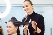 Competent hairdresser cutting and styling hair of woman in her shop poster