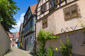 Small Town Kaysersberg , Region Alsace. France. Narrow Street Of Medieval Centre With Colorful Half- poster