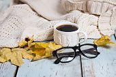 Warm White Knitted Plaid, Coffee, Phone, Glasses, Autumn Leaves On A Wooden Background. Reading In T poster