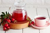 Cup of rose hip tea and fresh rose hips beside it poster