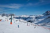 View of a ski resort piste with people skiing in Dolomites in Italy. Canazei, Italy poster